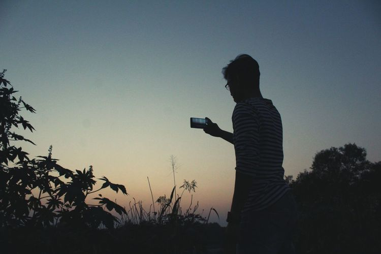 Silhouette of man photographing at sunset