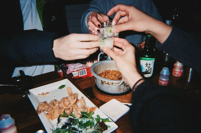 Midsection of people holding drink on table