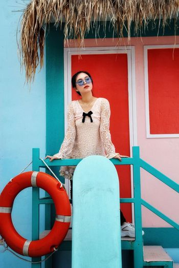 Young woman standing in front of a colorful beach hut