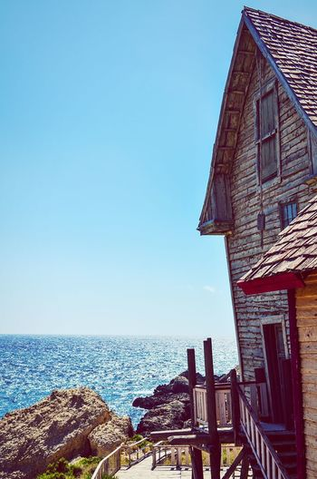 Rustic dreams. House By The Sea Wooden House Ocean View Front Porch Sea View Sea And Sky Blue Sky Rustic House Stairs And Steps Malta Anchor Bay Popeye Village Mediterranean  Building Exterior Clear Sky Sunny Vacation Horizon Over Water Calm Sea Summer Vertical Rocks And Water Shore Seascape