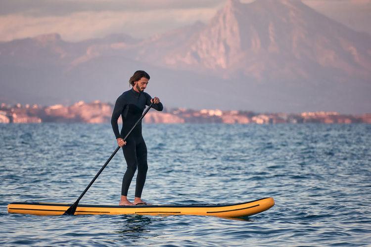 Full length of man standing in sea against sky during sunset