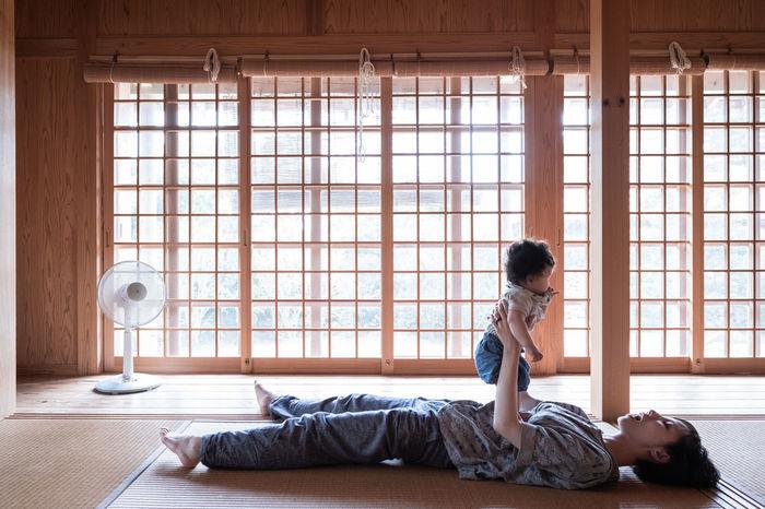 SIDE VIEW OF WOMAN LYING IN WINDOW