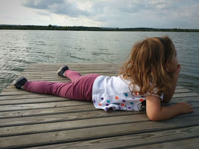 Lying Down Summer Vacations One Person Child Little Girl Beach Low Angle View Quiet Moments Quiet Tired Relaxing View Relaxing Moments Relaxing Time Lakeside Lake View Lying On The Beach Lying On The Floor One Girl Only Lake Waterfront Beachside Childhood Simple Moment Water