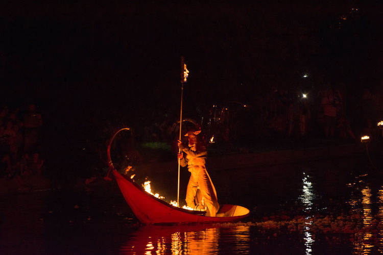 Illuminated boat in river against sky at night