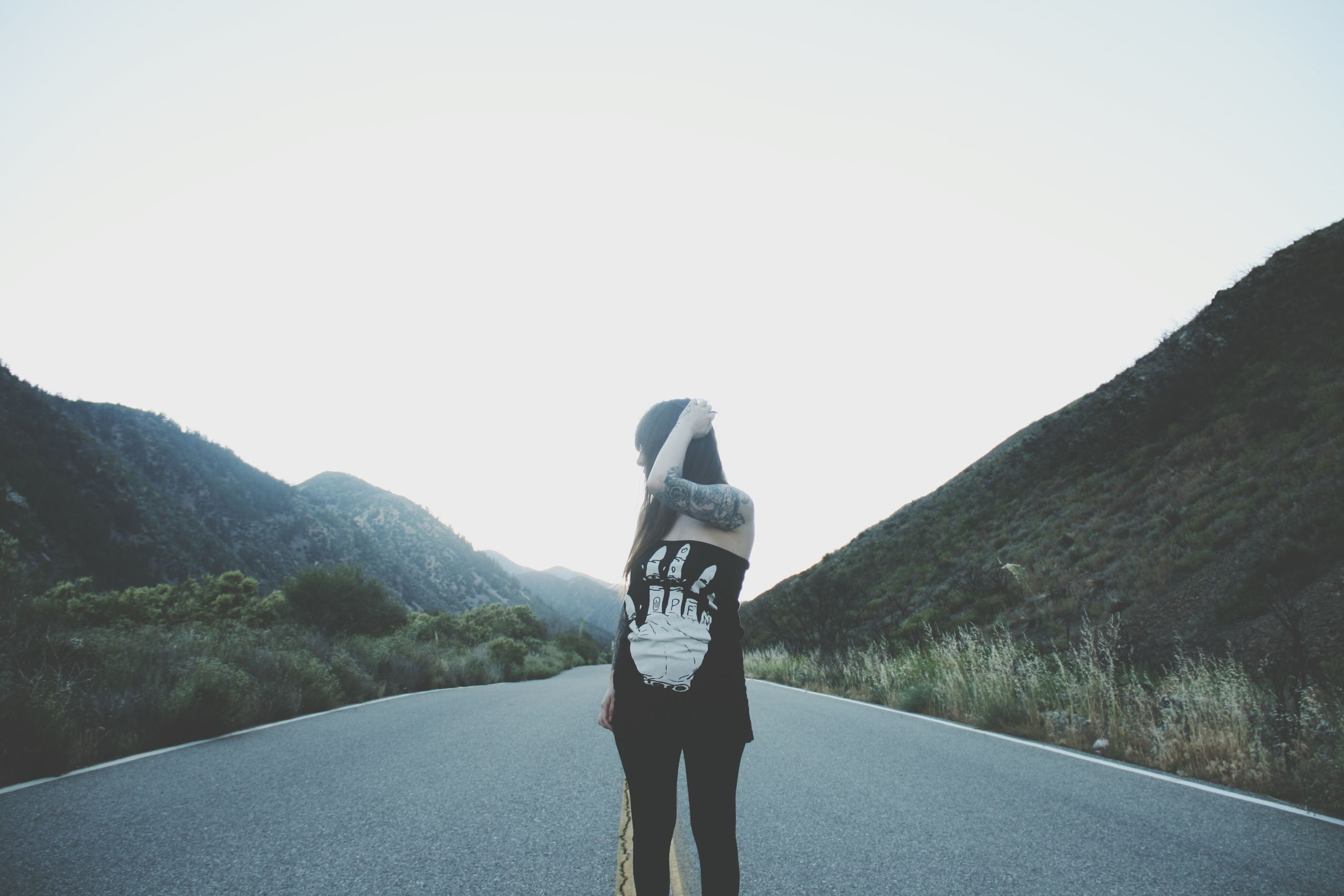 rear view, road, mountain, clear sky, real people, outdoors, one person, landscape, day, nature, walking, lifestyles, leisure activity, full length, sky, standing, young adult, women, young women, beauty in nature, people
