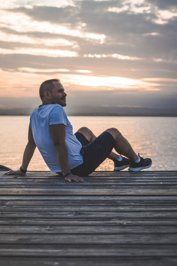 Man sitting on pier against cloudy sky during sunset