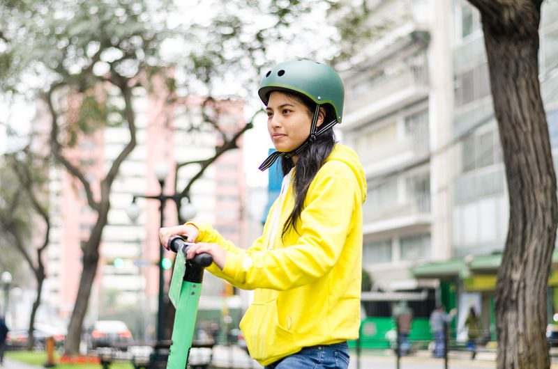 Young woman with push scooter in city