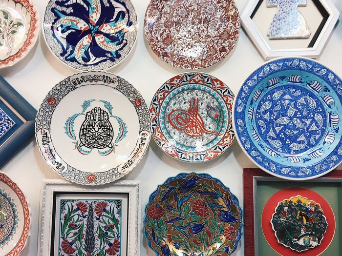 Close-up of designed crockery on wall at market