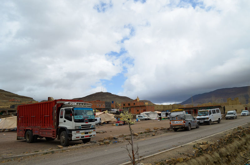 Vehicles on road against cloudy sky