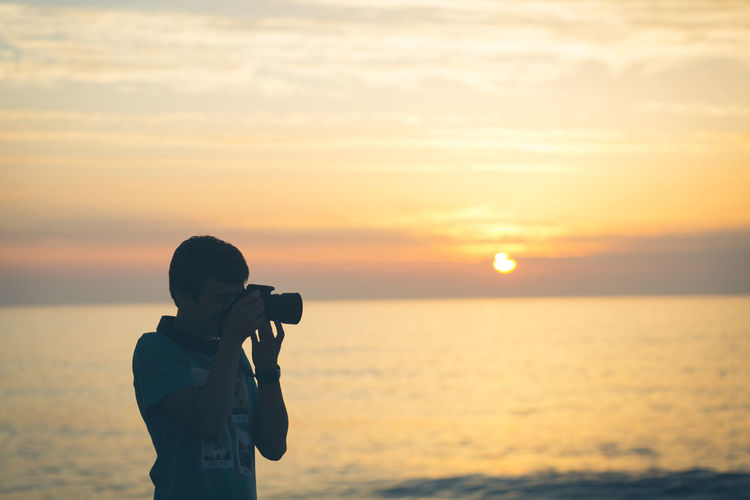 Photographer photographing by sea against sky during sunset