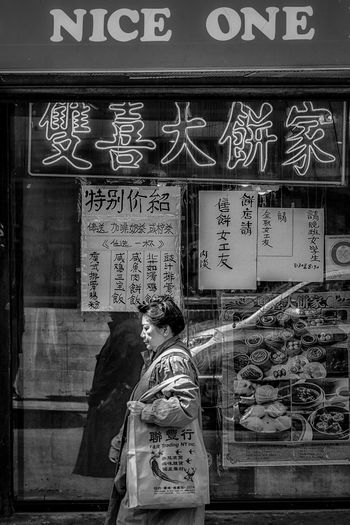 A woman in the front a Chinese store Text Communication One Person Western Script Real People Day The Street Photographer - 2018 EyeEm Awards Number Rear View Sign Non-western Script Architecture Waist Up Casual Clothing Men Script Lifestyles Adult Information Women