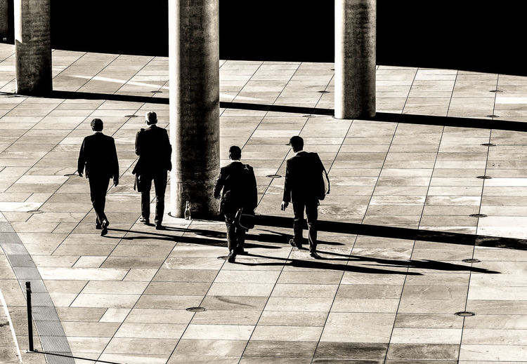 High Angle View Of Businessmen Walking On Footpath In City