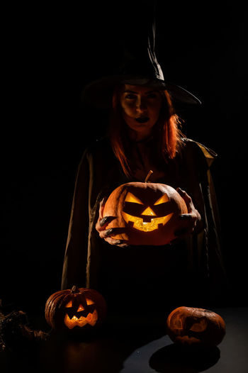 Portrait of a girl holding pumpkin at home