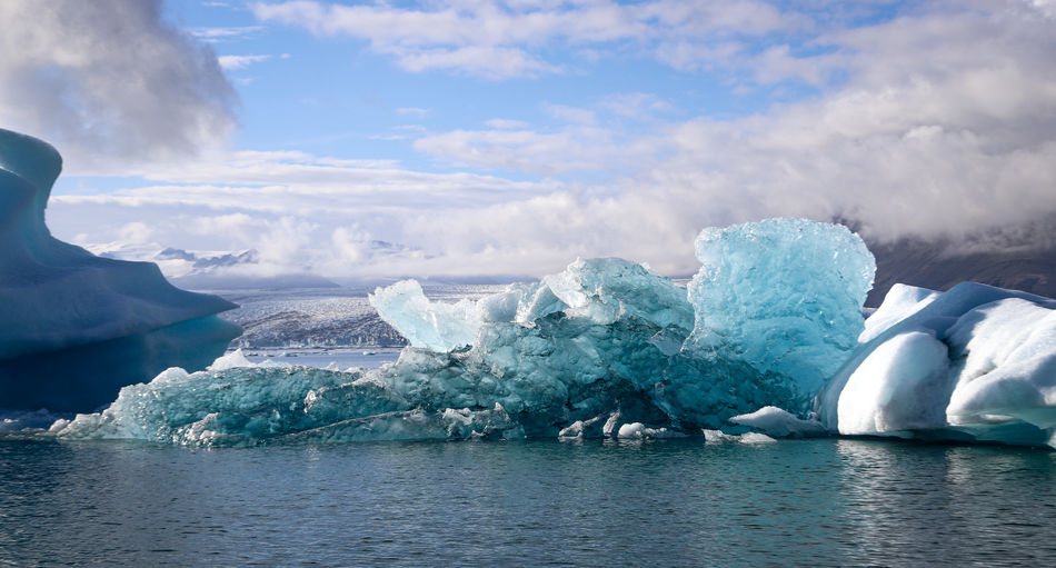 Scenic view of iceberg on glacier lake against sky during winter