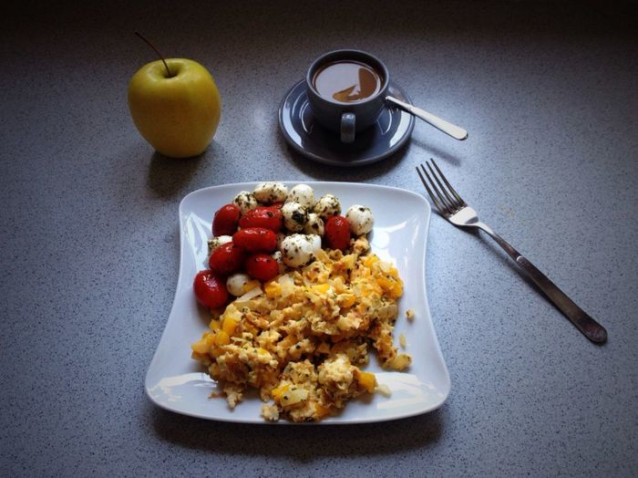 Food served on plate by apple and espresso