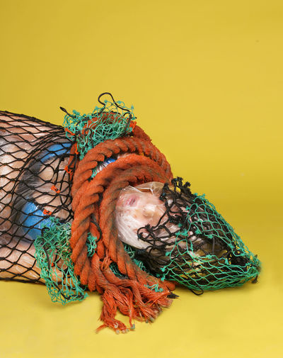 Dead woman trapped in rope and fishing net against yellow background
