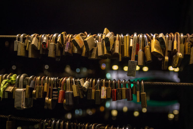 Close-up of padlocks hanging on railings in city at night