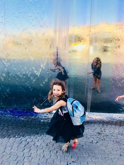 High angle view of smiling girl walking on footpath by glass