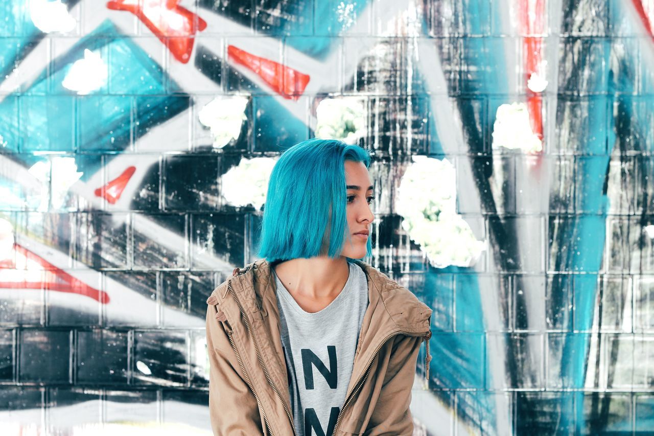 Woman with dyed hair sitting against graffiti wall