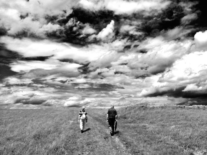Two elderly people walking under dramatic sky / ein älteres Paar wandert unter einem dramatischen Himmel über ein Feld Elderly Rentner Couple Black And White Landschaft Schwarzweiß Cloud - Sky Sky Nature Day Real People Leisure Activity Field Walking Togetherness Rear View Two People Beauty In Nature Landscape