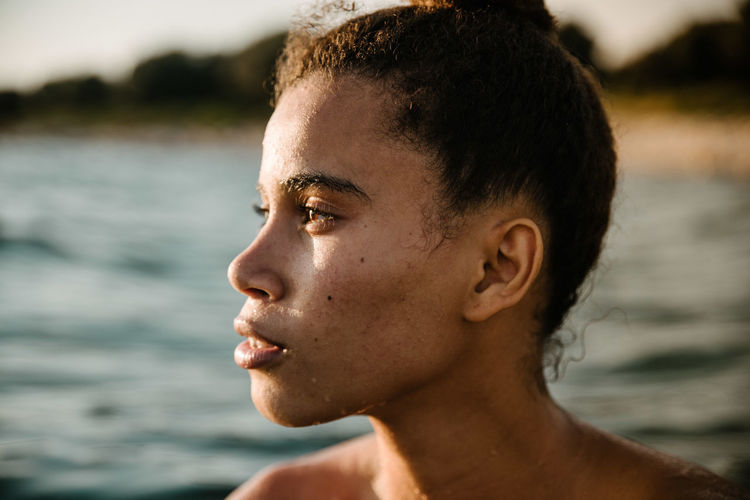 Close-Up Of Thoughtful Young Woman Swimming In Sea