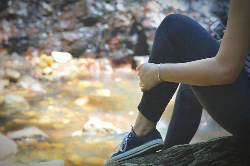 Low Section Of Woman Sitting On Rock