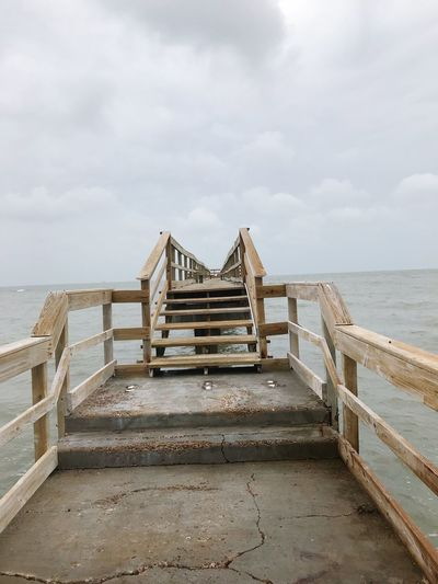 Wooden pier on beach against sky