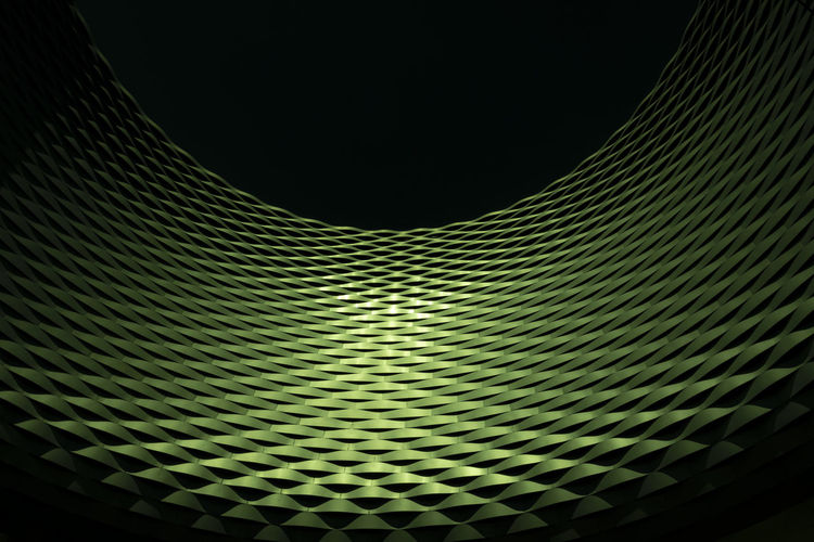 Low angle view of illuminated lights against black background