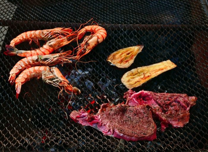 High Angle View Of Steaks And Shrimps On Barbeque Grill