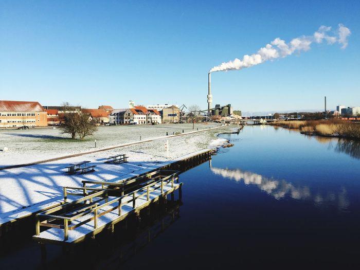 Smoke stack on riverbank emitting smoke against clear blue sky