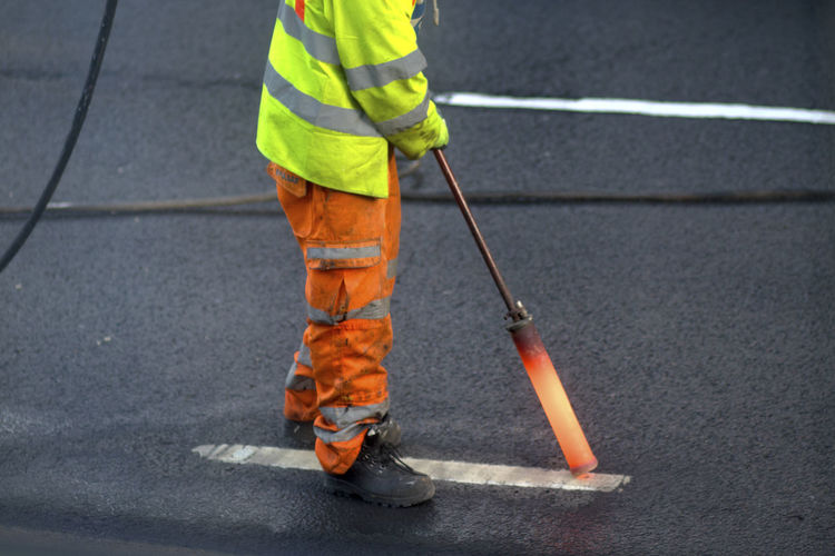Low section of man working on road