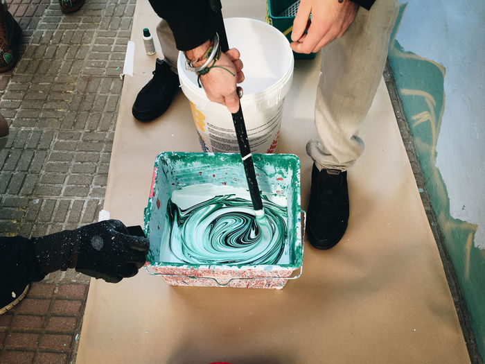 Low section of people standing by paint bucket
