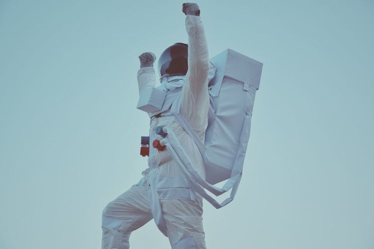 Low angle view of astronaut statue against clear sky