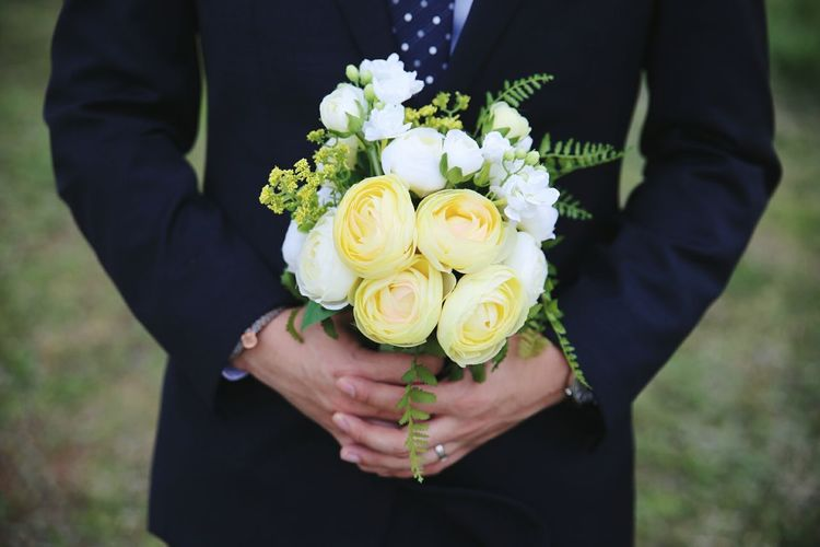 Close-up of man holding bouquet