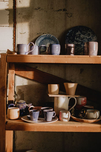 Film-look filtered pictures of beautifully designed hand-crafted pottery cups and dishes on shelves in rustic styled countryside kitchen Still Life No People Cup Kitchen Utensil Indoors  Film Photography Filtered Image Ceramics Ceramic Art Porcelain  Handmade Hand Craft Home is Where the Art is Clay Work kitchen utensils Kitchen Art Kitchenware Pottery Colors Homemade Home Sweet Home Household Equipment Shelf Domestic Kitchen Teapot Bowl Kitchen Crockery Rustic Old-fashioned Country Life