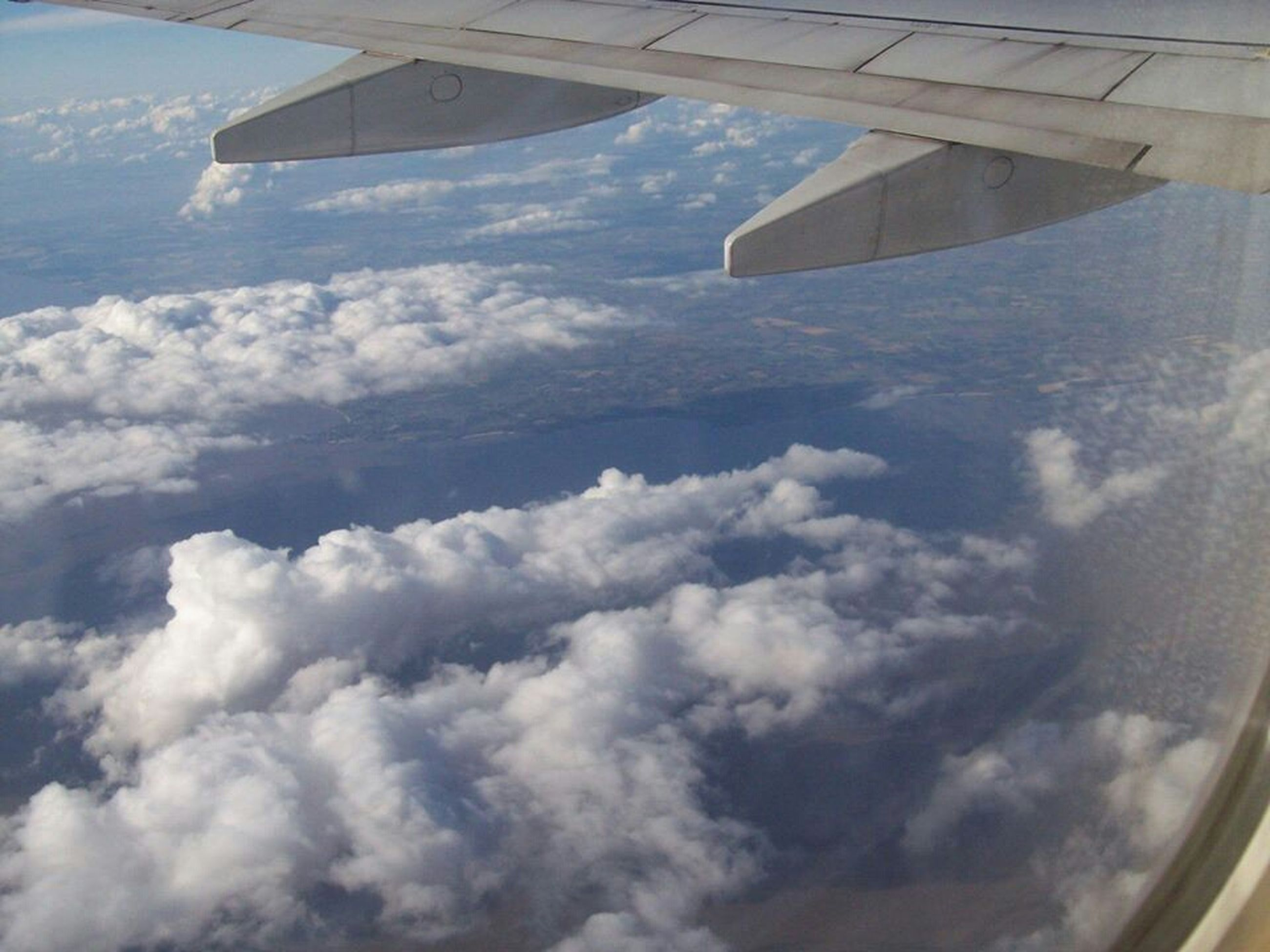 airplane, transportation, air vehicle, aircraft wing, mode of transport, part of, cropped, sky, flying, aerial view, cloud - sky, travel, scenics, nature, beauty in nature, cloud, journey, mid-air, vehicle part, cloudscape