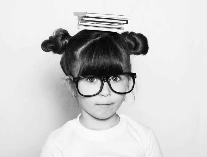 Portrait of cute nerd girl balancing books on head against white background