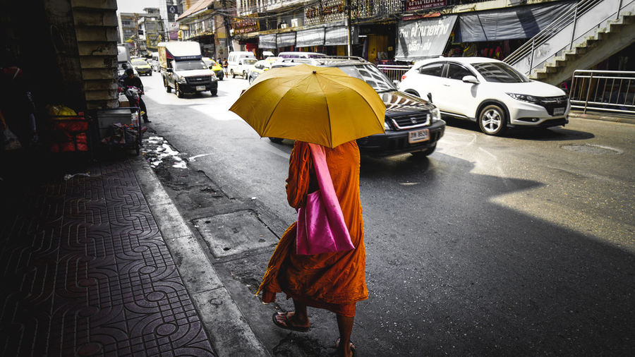 Rear view of monk walking under umbrella on street during sunny day