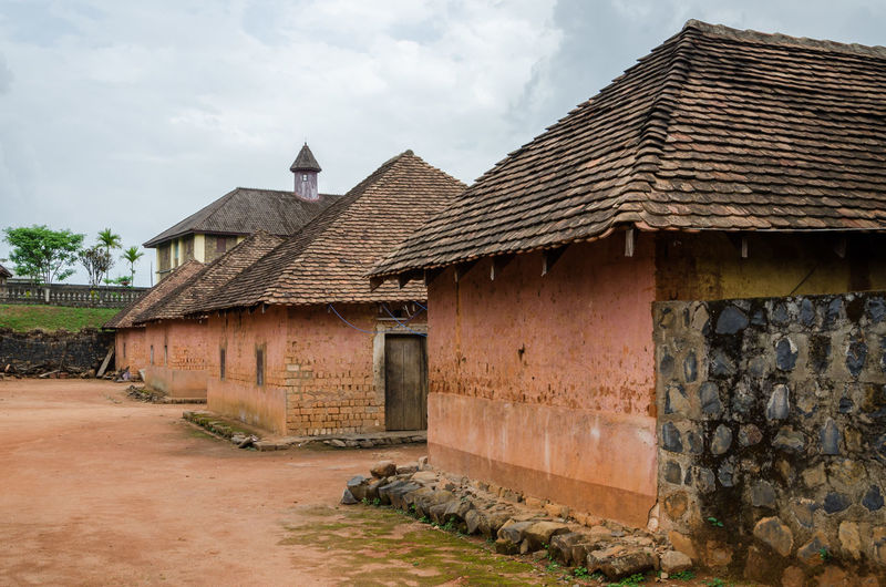 Traditional and historical palace of the Fon of Bafut with brick and tile buildings and jungle environment, Cameroon, Africa African Architecture Cameroon Cloudy Home Africa Architecture Brick Building Building Exterior Built Structure Cameroon Highlands Clouds And Sky Day House No People Outdoors Palace Sky
