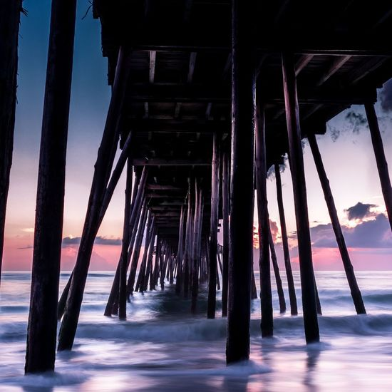 Long exposure sunrise under an ocean pier. Sunrise Coastal Coastline Outer Banks, NC Outdoors Reflection Nightphotography Nature Sea Beach Water Business Finance And Industry Architecture Built Structure Landscape Calm Wooden Post Horizon Over Water Seascape Wave Tide Surf Ocean Shore Coast Tranquility Tranquil Scene Scenics