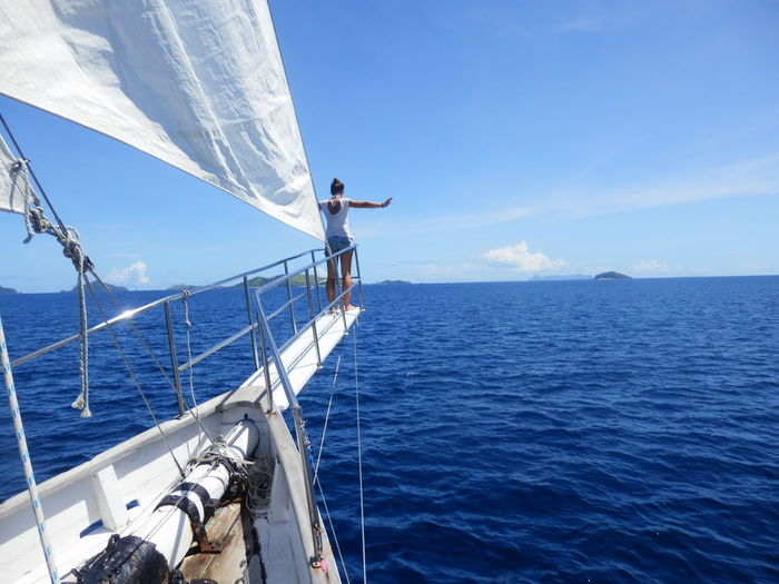 Rear View Of Young Woman With Arms Outstretched Sailing On Sea Against Blue Sky