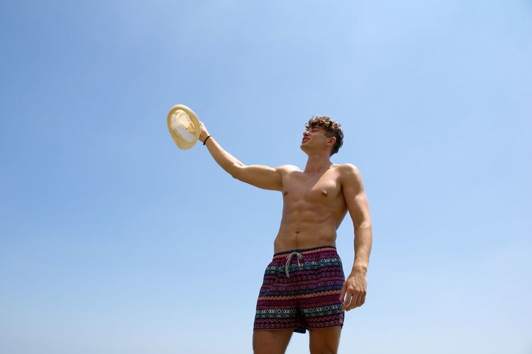 Low angle view of shirtless man with hat standing against clear blue sky