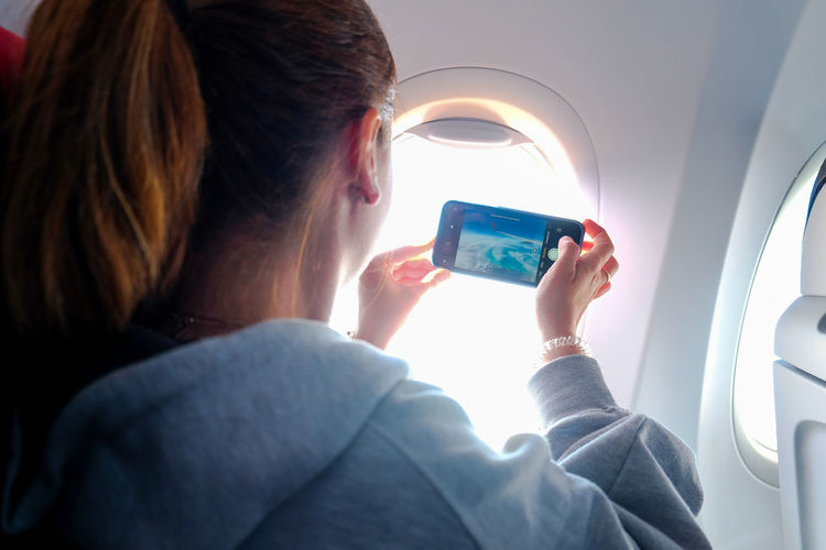 Rear view of man using mobile phone in airplane