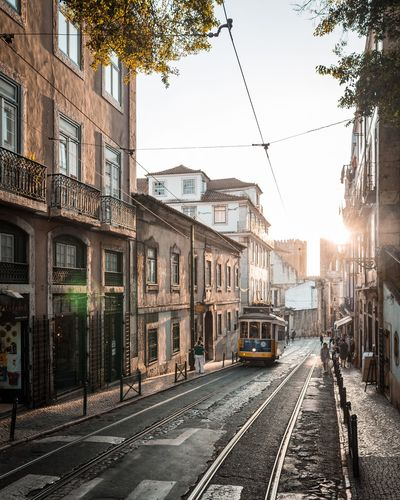sun and tram. Railroad Track Transportation Rail Transportation Tramway Public Transportation City Train - Vehicle Mode Of Transport Building Exterior Architecture Street Built Structure Outdoors Sky Cable Day Travel Destinations No People Lisbon - Portugal