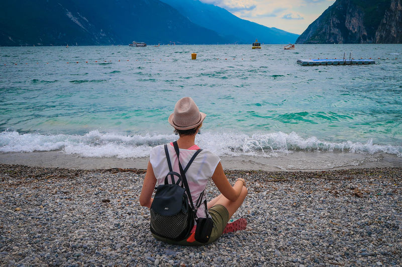 Rear view of woman looking at lake by mountains while sitting on pebbles