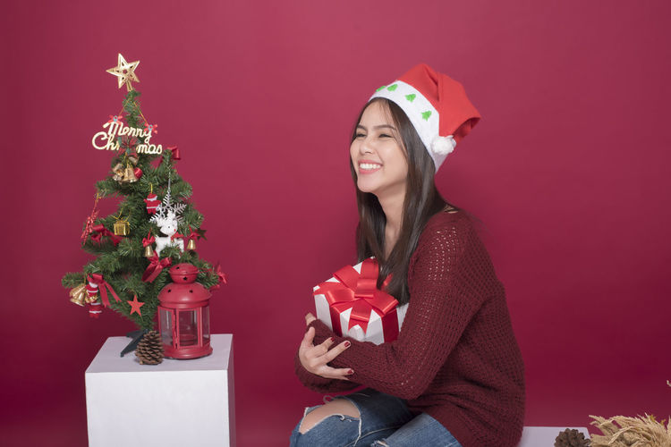 Young Woman With Christmas Decoration Against Maroon Backdrop