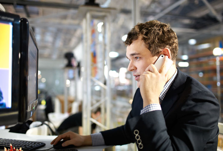 Side View Of Businessman Talking On Phone While Using Computer At Office