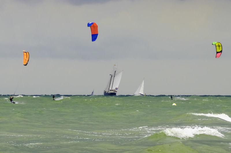 Kite flying over sea against sky