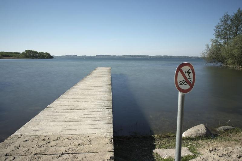 KÖHN-PÜLSEN, KREIS PLÖN, SCHLESWIG-HOLSTEIN: Weit ragt ein hoelzerner Steg an der Puelsener Badestelle vom Strand aus in den Selenter See hinein, ein rot-weisses Verbotsschild verbietet das Springen. Photograph (c) 2011 Kay-Christian Heine Caution Sign Footbridge Gangplank Jetty Lake Lakeshore Lakeside Lakeview Landing Stage Locked Out LockedOut No Swimming Schild Schwimmen Verboten See Sign Signs - Warnings Steg Symbolic  Verbotsschild Warning Sign Warnschild