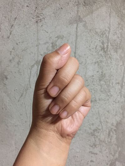 Cropped hand of woman clenching fist against wall
